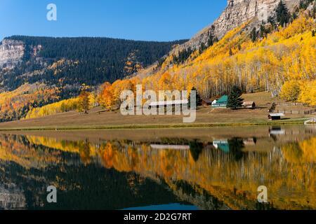 A cabin reflects a scenic autumn landscape in the water of a calm mountain lake near Durango, Colorado, USA.