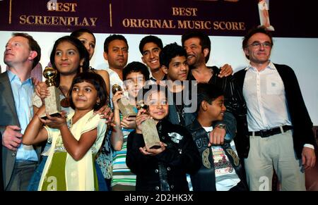 British director Danny Boyle (R) poses with his cast, including child actors Rubina Ali (front left holding Golden Globe) and Ayusha (front centre holding Golden Globe), during a news conference for their new film 'Slumdog Millionaire' in Mumbai January 20, 2009. Boyle's Golden Globe award-winning film will be released in India on January 23. REUTERS/Punit Paranjpe (INDIA)