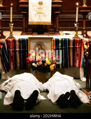 Married deacons Dominic Riccio (L) and Raymond Grosswirth lie prostrate before a picture of the Virgin Mary during their ordination ceremony performed by excommunicated Roman Catholic Archbishop Emmanuel Milingo at the Trinity Reformed Church in West New York, New Jersey, December 10, 2006. Milingo, the founder of 'Married Priests Now!', a group pressuring the Vatican to make priest celibacy optional, ordained the two married clergymen as priests on Sunday, defying the Vatican over the controversial issue of celibacy within the priesthood. REUTERS/Jeff Zelevansky (UNITED STATES) - Stock Photo