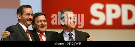Franz Muentefering (R) outgoing leader of Germany's Social Democratic Party (SPD), outgoing Chancellor Gerhard Schroeder and designated party leader Mathias Platzeck (L) receive applause from delegates at the SPD meeting in Karlsruhe, November 14, 2005. Stock Photo