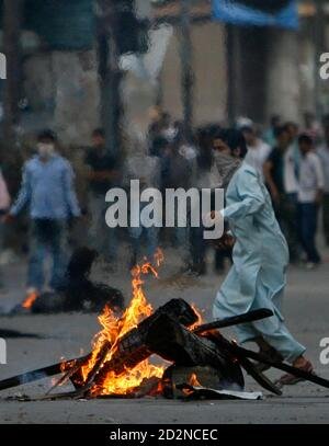 A Kashmiri protester carrying stones runs behind a fire set up during a protest in Srinagar July 8, 2009. Indian police fired shots into the air and used tear gas to disperse hundreds of angry demonstrators who torched police vehicle and pelted stones in Kashmir's main city protesting against the death of a student who was killed by police after his arrest, residents said. Police however denied the charge and said the 20-year-old student, Asrar Ahmad, was murdered by unidentified criminals. Protesters also burned tyres, brought traffic to a halt and forced shops and businesses to shut down in  - Stock Photo