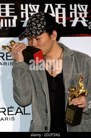 Taiwan's lyricist Fang Wen-shan kisses his trophy after winning Best Original Film Song Lyric for the film 'Secret' at the 44th Golden Horse Awards in Taipei December 8, 2007. Fang also collected Jay Chou's Composer and Performer award in the same category.  REUTERS/Bobby Yip (TAIWAN) - Stock Photo