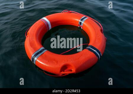 Orange lifebuoy in water. Life saving and help concept. Risks and safety in the water during summer season. - Stock Photo
