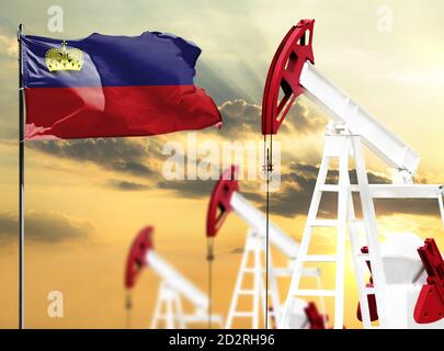 Oil rigs against the backdrop of the colorful sky and a flagpole with the flag of Liechtenstein. The concept of oil production, minerals, development