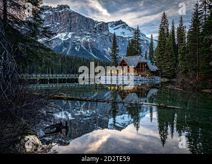 Magnificent scenery of Emerald Lake with bridge over water and wooden house on shore surrounded by green pine forest against rocky mountains covered with snow in Yoho National Park in Canada - Stock Photo