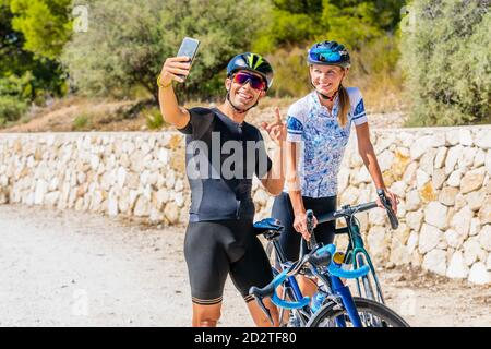 Happy young active man and woman in sportswear and protective helmets taking selfie on smartphone while standing with bikes on country road and preparing for riding - Stock Photo