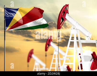 Oil rigs against the backdrop of the colorful sky and a flagpole with the flag of Seychelles. The concept of oil production, minerals, development of