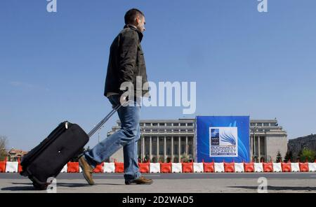 A man walks in Victoria square in front of a banner advertising upcoming NATO Summit during a rehearsal for traffic restrictions in Bucharest March 29, 2008. Romania's capital city Bucharest faces stringent security measures and traffic chaos during the April 2-4 NATO Summit. More than 30,000 personnel have been drafted to secure the bustling city and 6,500 delegates and journalists.  REUTERS/Bogdan Cristel (ROMANIA)