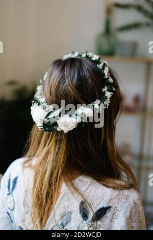 Back view of anonymous female wearing tender wreath with white rose flowers standing in flat - Stock Photo
