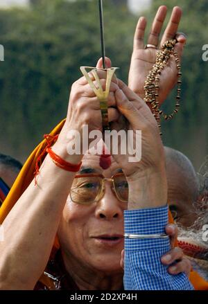 Tibetan spiritual leader Dalai Lama holds a sword presented to him by a representative of India's Sikh community, after a prayer meeting for those who lost their lives during China's crackdown of protests in Tibet, at the memorial of Mahatma Gandhi at Rajghat in New Delhi March 29, 2008. REUTERS/Adnan Abidi (INDIA) - Stock Photo