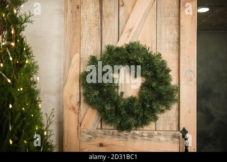 A green Christmas wreath made of pine needles hangs on the wooden eco door. Festive home decoration, decorated with a garland with lights. Textured - Stock Photo