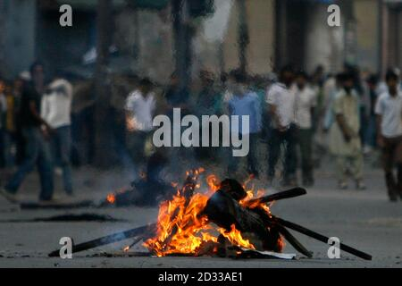 Kashmiri protesters stand behind a fire set up during a protest in Srinagar July 8, 2009. Indian police fired shots into the air and used tear gas to disperse hundreds of angry demonstrators who torched police vehicle and pelted stones in Kashmir's main city protesting against the death of a student who was killed by police after his arrest, residents said. Police however denied the charge and said the 20-year-old student, Asrar Ahmad, was murdered by unidentified criminals. Protesters also burned tyres, brought traffic to a halt and forced shops and businesses to shut down in the heart of Sri - Stock Photo