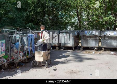 old homeless woman begging through the trash heaps, standing at the dumpster with waste in the landfill Feeling cold. Portrait of a cheerless aged wom Stock Photo
