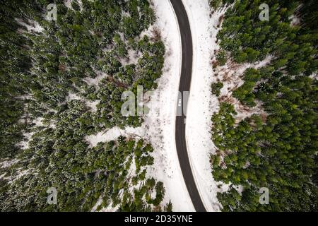 Flight over the winter mountains with road serpentine and snowy forest. Top down view. Landscape photography - Stock Photo