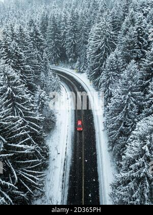 Aerial view of snow covered forest.A red car going between the trees on asphalt road. Nature travel concept. - Stock Photo