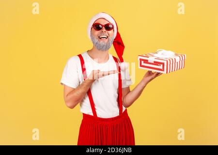 Extremely happy gray bearded man in sunglasses and santa claus costume showing giftbox looking at camera with toothy smile. Indoor studio shot isolate