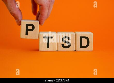 Concept words 'PTSD, post-traumatic stress disorder' on cubes on a beautiful orange background. Male hand. Copy space.