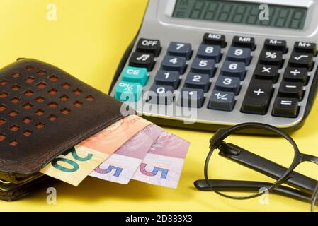 money coming out of wallet with blurred pocket calculator in the background.