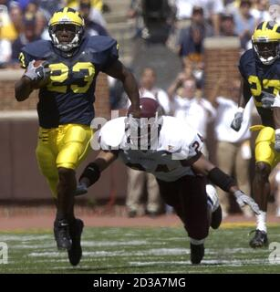University of Michigan running back Chris Perry (23) carries the ball for 33 yards before being tripped up by Central Michigan James King (24) in the third quarter of the game at Michigan Stadium in Ann Arbor, August 30, 2003. Michigan beat Central 45-7. REUTERS/Rebecca Cook  RC