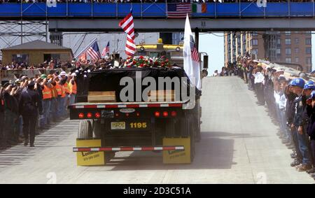 A flatbed truck, carrying the last steel beam from the wreckage of the World Trade Center disaster, is driven up a ramp from ground zero as uniformed officers from New York's emergency services, police and fire departmentd salute during a ceremony marking the end of the recovery effort at the World Trade Center site in New York, May 30, 2002. The beam is wrapped in black bunting. REUTERS/Mike Segar  MS/SV