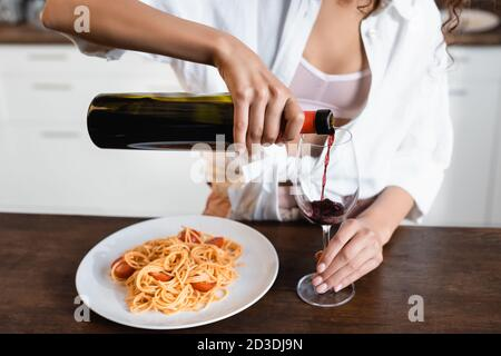 cropped view of woman pouring red wine in glass near plate with spaghetti Stock Photo