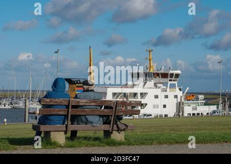 Old couple sitting on bench overlooking harbour.  Norddeich. East Frisia. Germany Stock Photo