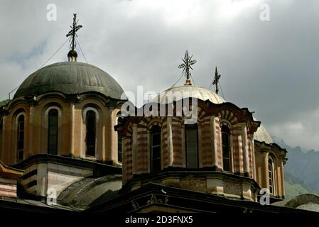 A view of the dome of main church at the Rila Monastery, some 125 km south-west from Sofia on June 18, 2003. Rila Monastery, the biggest Bulgarian monastery was founded in the l0th century by the Bulgarian monk St. John of Rila and was rebuilt in the l3th -l4th century. In the l5th century, when Bulgaria fell to the Ottoman Turks, the monastery was abandoned for a short time but in the second half of the same century it was restored to a new life. Its thorough renovation began in the early l9th century. - Stock Photo