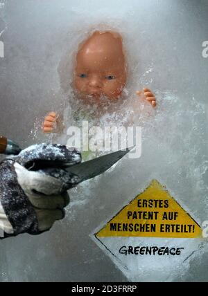 A Greenpeace activist works on an ice block containing a baby doll and a sign reading 'First Patent Granted on Humans' during a demonstration in front of the European Patent Office in Munich, April 5, 2004. Greenpeace blocked the entrance of the Patent Office with walls of stones and ice blocks to protest against scientific patents on embryos. REUTERS/Alexandra Winkler  AX/AKW