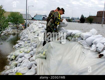First Sgt. Scott Wolf (L) and First Lt. Eric Rant (R) of the Iowa Army National Guard shore up a sandbag levee built at the edge of the downtown business district in Davenport, Iowa as floodwaters from the Mississippi River continue to rise, April 23, 2001. The river is predicted to crest in Davenport late April 24.  SO/ME - Stock Photo