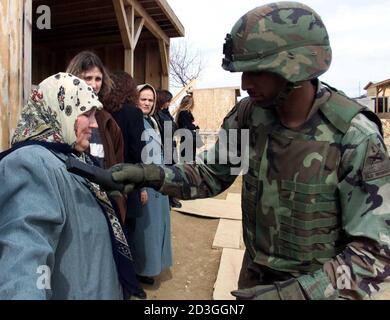 A US KFOR soldier searches ethnic Albanian woman at a checkpoint on the border with Serbia at Mucibabe March 13, 2001. A ceasefire between ethnic Albanian guerrillas and state security forces was holding on Tuesday in Serbia's volatile Presevo Valley region bordering Kosovo and Macedonia. The area has remained quiet since the ceasefire came into force one minute after midnight, but officials on all sides said it remained a challenge to bring lasting peace to the area after more than a year of sporadic violence.  PEK/ - Stock Photo