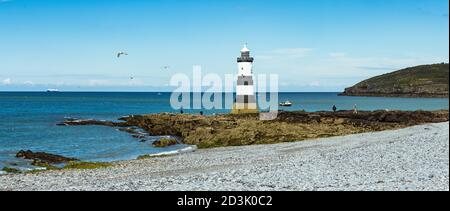 Trwyn Du Lighthouse at Penmon, Anglesey, Wales with the ferry used to carry Airbus wings to France waiting on the tide offshore - Stock Photo