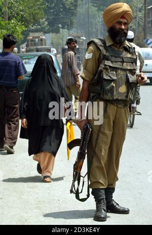 A Kashmiri Muslim woman walks past an Indian Border Security Force soldier in Srinagar, July 21, 2005. Security has been tightened in Srinagar after a suicide bomber slammed a car into a military jeep in Srinagar on Wednesday, killing six people including himself, a civilian and four soldiers, and wounding 17, authorities said. REUTERS/Fayaz Kabli  FK/JK - Stock Photo