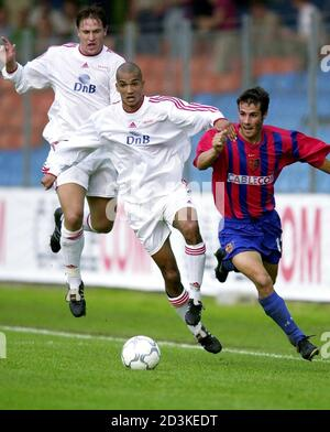 FC Basel's Sebastian Barberis (R) is held by Alex Valencia (M) of Norway's SK Brann Bergen as Thorstein Helstad (L) looks on during the UEFA Cup first round first leg match FC Basel vs. SK Brann Bergen in Zurich, Switzerland, September 12, 2000.  SIB/HM/JRE - Stock Photo
