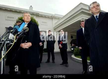 Standing before the microphones, Polish President Aleksander Kwasniewski speaks to the media after his meeting with President George W. Bush at the White House January 14, 2003. Kwasniewski, on a two-day working visit to Washington, met with Bush to discuss the war on terrorism. REUTERS/Kevin Lamarque  KL