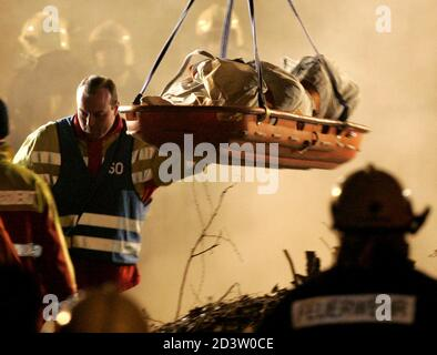 The body of a firefighter is lifted from an underground car park after the roof collapsed and buried up to seven fire fighters in the town of Gretzenbach between the cities of Basel and Zurich November 27, 2004. Construction experts, earthquake rescue specialists and other fire and rescue personnel raced against time to find the men who had been battling a fire in the residential car park when the roof caved in and trapped them in its rubble. Pictures of the month November 2004 REUTERS/Ruben Sprich  RS/WS