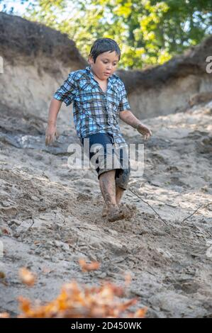 A young boy covered in sand walks down a steep dune on the shores of Lake Michigan USA - Stock Photo