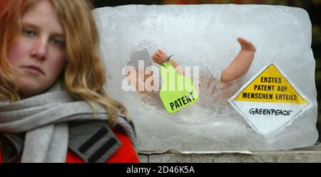A Greenpeace activist stands next to an ice block containing a baby doll and a sign reading 'First Patent Granted on Humans' during a demonstration in front of the European Patent Office in Munich, April 5, 2004. Greenpeace blocked the entrance of the Patent Office with walls of stones and ice blocks to protest against scientific patents on embryos. REUTERS/Alexandra Winkler  AX/akw