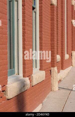 Antique red painted brick wall texture building background with windows in full sunlight with copy space - Stock Photo