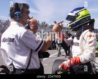 Brazilian Cristiano da Matta (R) celebrates with crew members after the first qualifying session for the Molson Indy in Montreal, Quebec, August 23, 2002. Da Matta took the provisional pole position with a time of one minute 19.465 seconds. It is the first time the CART series has come to Montreal with the race being run on August 25. REUTERS/Jim Young  JY Stock Photo