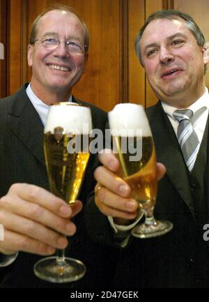 Ulrich Kallmeyer, general adviser of German family-owned food giant Dr Oetker food group and Radeberger brewery (L) and Michael Hollmann, CEO of brewer Brau and Brunnen AG toast with their company's beers after they announced the merger of Brau and Brunnen with the Oetker group during a news conference in Frankfurt February 13, 2004. - Stock Photo