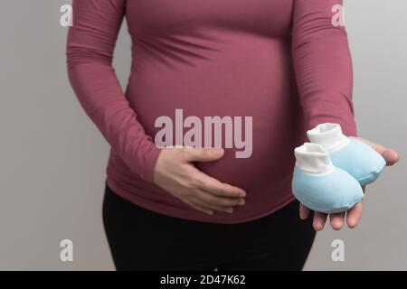Close up body of Asian pregnant woman with red long sleeved t-shirt holding the blue cute baby shoe, studio light portrait and copy space on grey back - Stock Photo