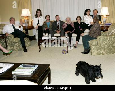 U.S. President George W. Bush watches returns from the presidential election with his family at the White House.  Barney, pet terrier of the U.S. first family, walks away from a group picture of the Bush family including U.S. President George W. Bush (L) as they watch the election results of the 2004 presidential election in the West Sitting Hall of the White House residence November 2, 2004. Members of his family are daughter (L-R) daughter Barbara Bush, first lady Laura Bush, father and former President George Bush, first lady Barbara Bush, sister Doro, sister-in-law Maria Bush, brother Neil - Stock Photo