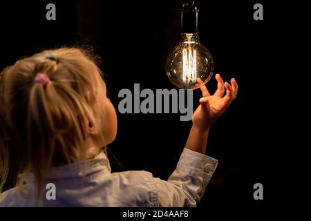 Cute adorable caucasian blond girl portrait smiling and holding in hand one of hanged edison light bulb at forest outdoor. Right solution choice