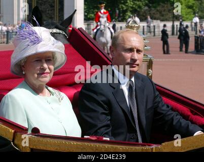 A carriage carrying Britain's Queen Elizabeth II and Russian President Vladimir Putin is escorted by royal guards to Buckingham Palace in central London June 24, 2003. [Putin is on the first state visit by a Russian leader since 1844, when Nicholas I visited the British Isles at the invitation of Queen Victoria.]