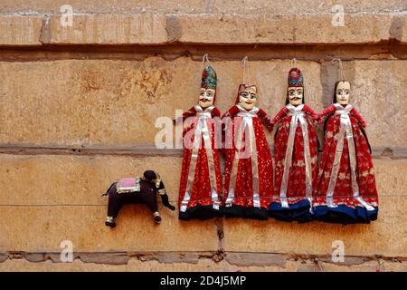 Colorful human shaped Puppets wearing colorful clothes hanging against the wall in Rajasthan India on 21 February 2018