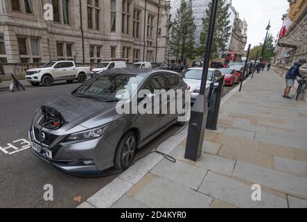 Nissan Leaf zero emission electric car charges kerbside on a pod point charging station at Whitehall Place, London, October 2020.
