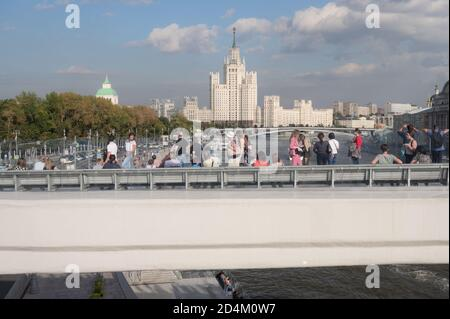 Tourists on the River Overlook, 70-metres long concrete console in Zaryadye park in central Moscow, Russia, against one of Seven Sisters skyscrapers