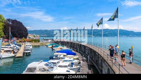 Lindau, Germany - July 19, 2019: Panorama of Lake Constance or Bodensee, people walk next to yachts in harbor. This old town is tourist attraction of