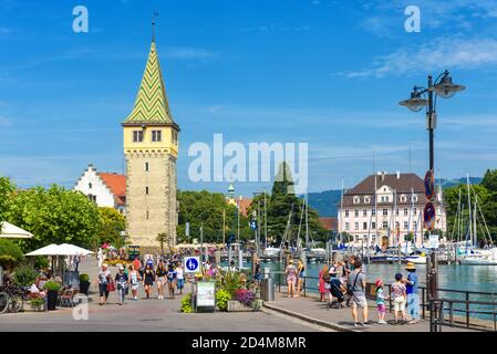 Lindau, Germany - July 19, 2019: Panorama of Lindau embankment with Mangturm Tower at Lake Constance or Bodensee, people walk next to harbor in summer