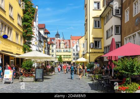 Lindau, Germany - July 19, 2019: Street in old town of Lindau, people walk next to shops, restaurants and cafes in summer. This city at Lake Constance